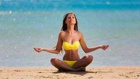 Brunette woman yellow swimsuit yoga Royalty Free Stock Images