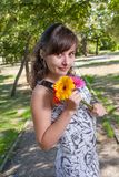 Brunette women in city park with flowers in her hands Royalty Free Stock Photos