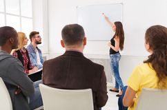 Brunette woman doing presentation in office. Brunette women doing presentation in office, showing at whiteboard copy space. Startup business meeting, sharing new stock image