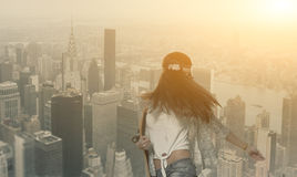 Brunette women with skateboard in her hands on NY Royalty Free Stock Photos