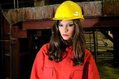 Brunette worker in heavy industry. Brunette worker  with yellow helmet and red equipment Stock Image