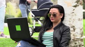 Brunette on the grass with a computer. Brunette works with a computer on the street stock footage
