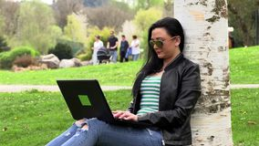 Brunette on the grass with a computer. Brunette works with a computer on the street stock video