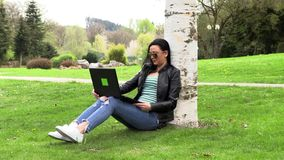 Brunette on the grass with a computer. Brunette works with a computer on the street stock video footage