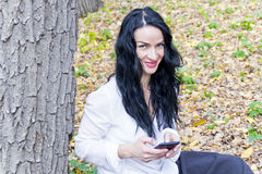 Brunette writing sms by cellular in autumn park Royalty Free Stock Photos