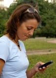 Brunette y teléfono celular Fotos de archivo libres de regalías