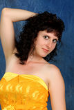 Brunette in a yellow dress on a blue background Royalty Free Stock Photos