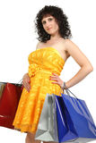 Brunette in a yellow dress with shopping bags Stock Image
