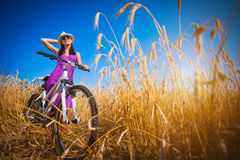 Brunette in a yellow field on a bike Stock Photo