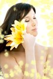 Brunette with yellow flowers in spa Stock Photos