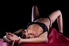 Sexy young woman lying on silk sheet Stock Images