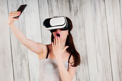 A pretty girl wearing VR glasses, excitedly holding her phone in royalty free stock photography