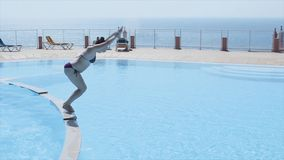 Brunette young girl dive into open swimming pool. Summer sunny day. Holidays. Splash. Blue water stock video