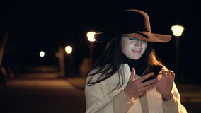 Brunette young girl in a hat and white coat check her phone and smiles in a night park stock video