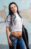 Brunette young girl in jean posing near wall. Brunette young girl in jean posing royalty free stock photo