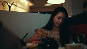 Brunette young girl sit at table in sushi restaurant. Smile. Talk with someone stock video
