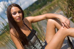 Brunette young girl sitting outdoors Stock Photo