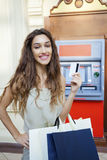 Brunette young lady using an automated teller machine Stock Images
