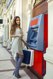 Brunette young lady using an automated teller machine Royalty Free Stock Photography