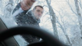 Brunette young man in black hood clean the windshield of the car from snow. Inside view.  stock footage