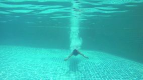 Brunette young slim woman jumps and swimming underwater in pool. 1920x1080