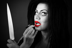 Brunette young woman applying lipstick using the knife as a mir Royalty Free Stock Photos