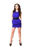 Brunette young woman in a blue dress posing on a white backgroun. Brunette young woman in a blue dress posing on white background Stock Photos