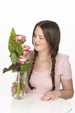 Brunette young woman enjoys a bouquet of roses Royalty Free Stock Photography