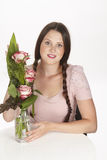 Brunette young woman enjoys a bouquet of roses Royalty Free Stock Photo