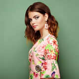 Brunette young woman in floral spring summer dress. Girl posing on a green background. Summer floral outfit. Stylish wavy hairstyle. Fashion photo. Brunette Royalty Free Stock Photo