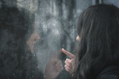 Young woman touching rainy window. Brunette young woman and her reflection on a window covered with raindrops Royalty Free Stock Photos