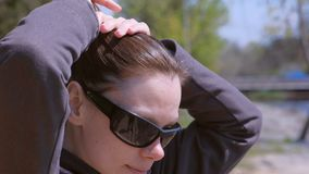 Portrait of brunette woman makes ponytail in city park, she does her hairs. Brunette young woman in jacket and sunglasses. Portrait of brunette woman makes stock footage