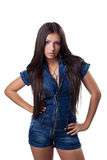 Brunette young woman in jeans overalls Stock Image
