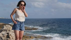 Brunette young woman in jeans shorts and silk top standing on the edge of rocky seashore, talking on the phone and smiling stock video footage