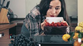 Brunette young woman making photos and videos of her raspberry cake with the smartphone. Amateur cooking, social media. Beautiful brunette girl making pictures royalty free stock photo