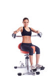 Brunette young woman on orange exerciser Royalty Free Stock Image
