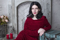 Brunette young woman in red dress sitting near the fireplace Stock Images