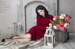 Brunette young woman in red dress sitting near the. Happy brunette woman sitting near the fireplace Royalty Free Stock Photos