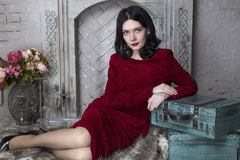 Brunette young woman in red dress sitting near the. Happy brunette woman sitting near the fireplace Royalty Free Stock Photo