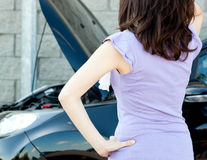 Brunette young woman standing in front of her car Stock Photo