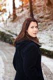 Young woman standing outdoors in the cold and looking scared. Brunette young woman standing outdoors in the cold and looking scared stock image