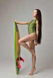 Brunette young woman walking with long hair and surfboard. Beautiful full body brunette young woman walking with long hair and surfboard over a gray background Royalty Free Stock Images