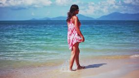 Brunette young woman walking on a tropical beach with amazing blue color the sea. 1920x1080 stock footage