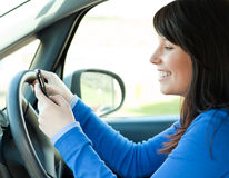 Brunette young woman writing a message in her car Royalty Free Stock Images