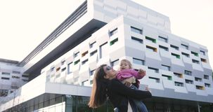 Brunette young women hugs, throw up little girl, urban background.  stock video footage