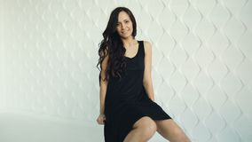 Brunette young women poses, smiling, waving hair, sitting and turning on the chair in black dress. White wall texture. Background stock video footage