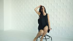 Brunette young women poses, smiling, waving hair, sitting and turning on the chair in black dress. White wall texture. Background stock footage
