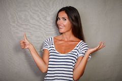 Brunette youngster standing with thumb up Stock Photo