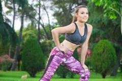 Brunette in zich het heldere sportkleding uitrekken in park Royalty-vrije Stock Foto's