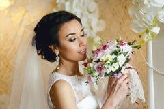 Brunettebraut mit Hochzeitsblumenstrauß stockbild